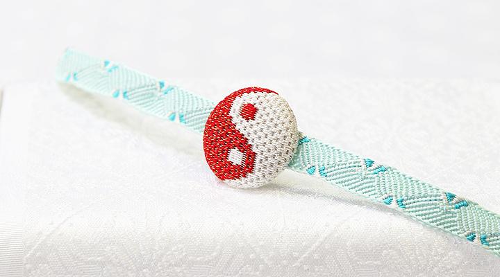 絽刺し帯留め 陰陽(赤/金) 紐を通したイメージ 正面